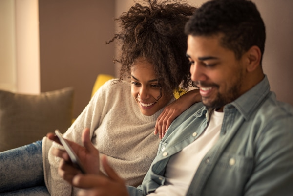 African american couple watching favorite TV show on a tablet.